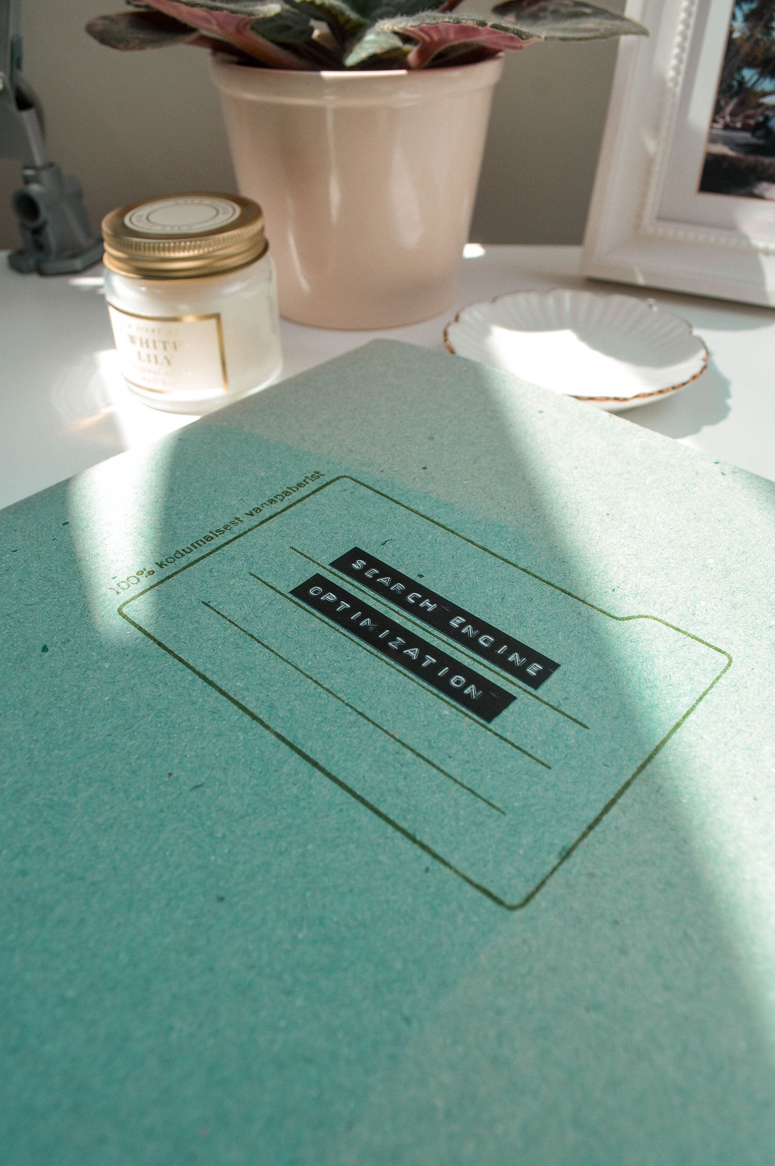 """Folder titled """"Search Engine Optimization"""" laying on the table, surrounded with decor"""